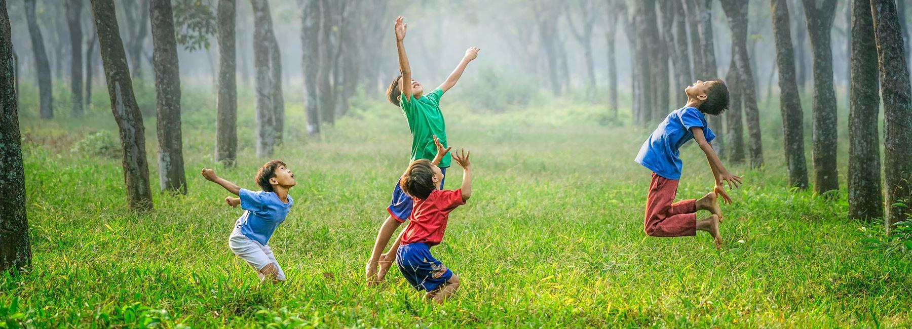 Barn som hoppar högt i gräset
