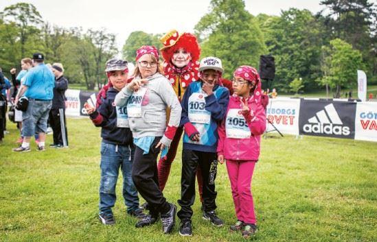 Unga deltagare i Specialvarver strå och poserar med en person utklädd till clown