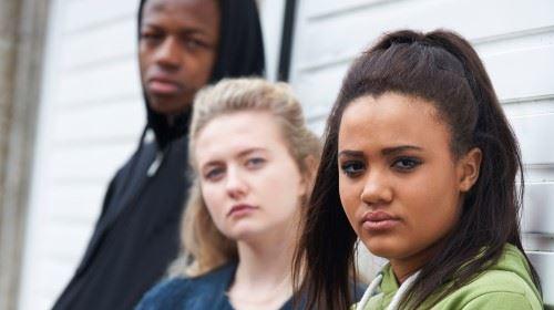 Tre ungdomar som står lutade mot en vägg och tittar in i kameran