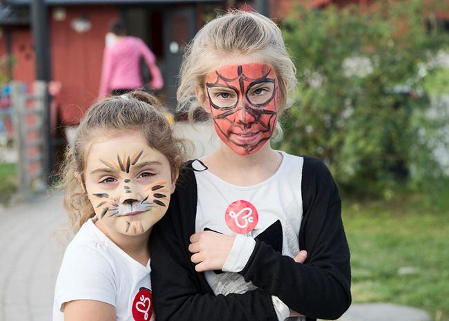 Två unga tjer som har fått varsin ansiktsmålning